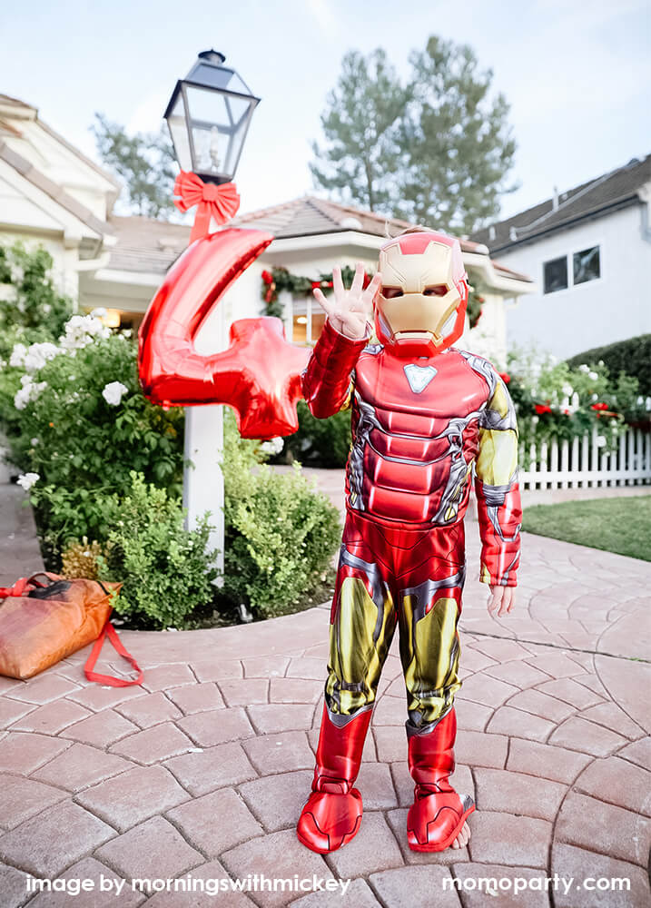 Boy dressed up as iron man for his superhero Avengers themed birthday party with a number 4 red foil balloon in the back