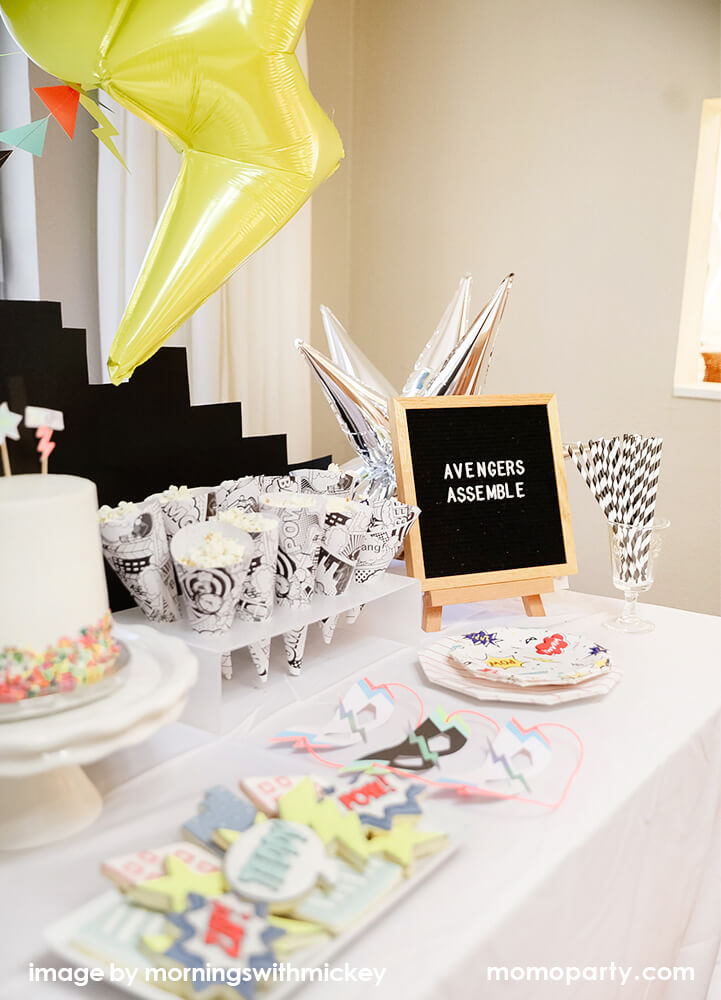 Kids superhero themed birthday party table with superhero themed tableware and masks by Momo Party
