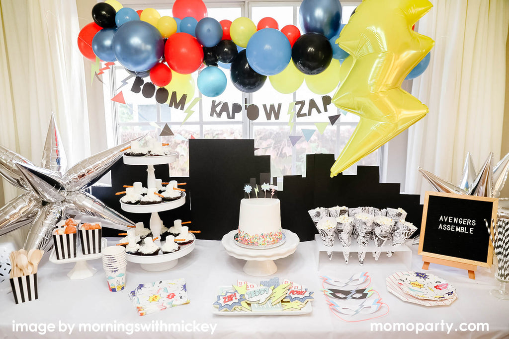 vintage retro superhero themed birthday party set up with black city backdrop and festive colorful balloon garland by Momo Party