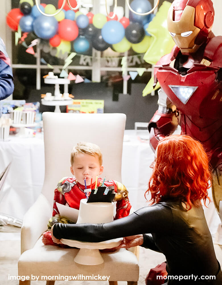 Boy blowing out birthday candles in a superhero themed birthday party with ironman standing next to him and festive balloon garland and party banners in the back