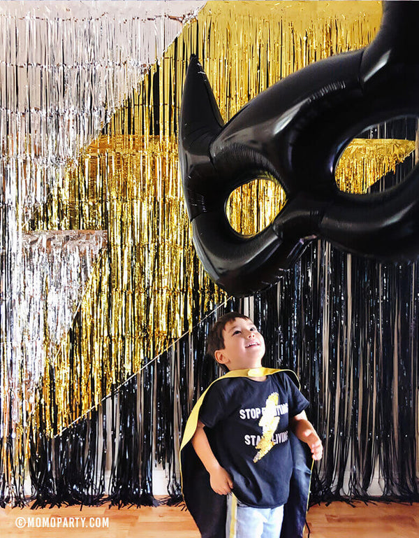 boy wear lighting bolt shirt and batman cape looking at 45' Huge Bat Mask Super Hero Batman Mylar Foil Balloon in from the lighting bolt fringe curtain backdrop at superhero birthday party