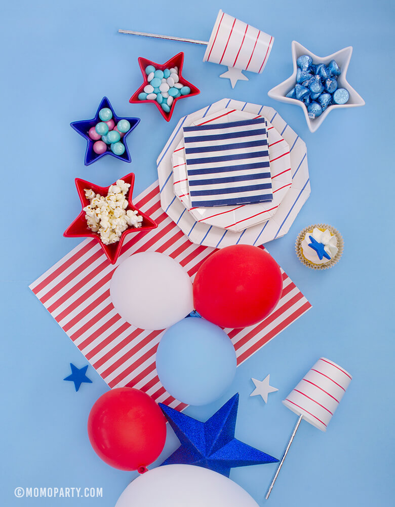 Morden 4th of July Table set up inspiration with Day dream society Blue Striped Large Plates, Red Striped Small Plate, Red Striped Cups, Blue, Red, White latex balloons, Star shaped bowl with candy and popcorn, cupcake with star topper over a blue background