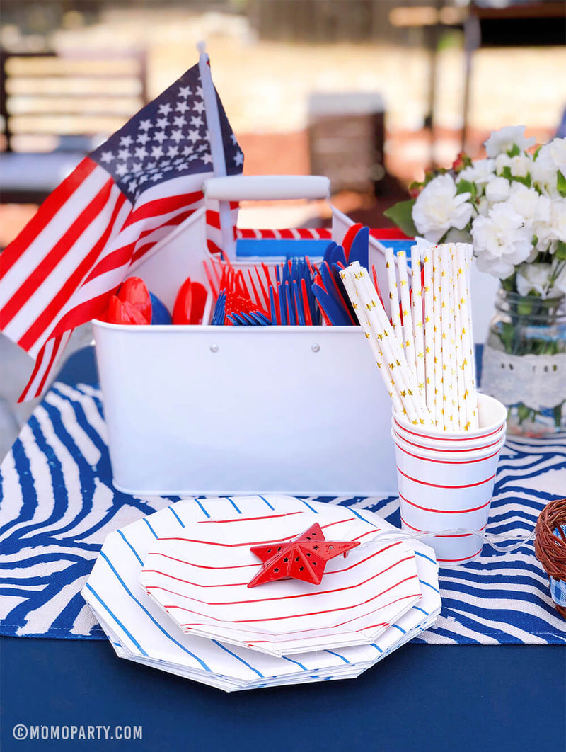 Morden backyard 4th of July Party table set up with Day dream society Blue Striped Large Plates, Red Striped Small Plate, Red Striped Cups, gold start print paper straw, American flag in the cutlery container, flowers on a blue strip table runner.