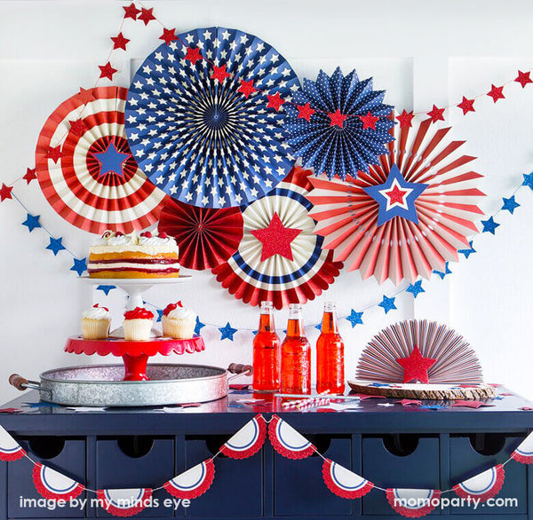 4th of July Patriotic party with  My mind's eye Stars & Stripes Party Paper Fans, blue  and red start mini garland as backdrop. there are cakes and cupcake on the white and red cake stand, red soda, straws, tablewares filled in the front of the blue table. This home set up are perfect for a 4th of july party at home