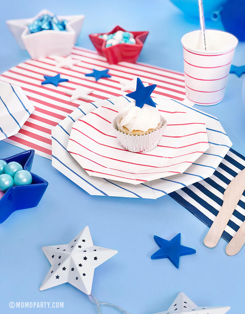 Morden 4th of July Table set up inspiration with Day dream society Blue Striped Large Plates, Red Striped Small Plate, Red Striped Cups, Silver Straw, Blue, Red, White latex balloons, Star shaped bowl with candy, cupcake with star topper over a blue background