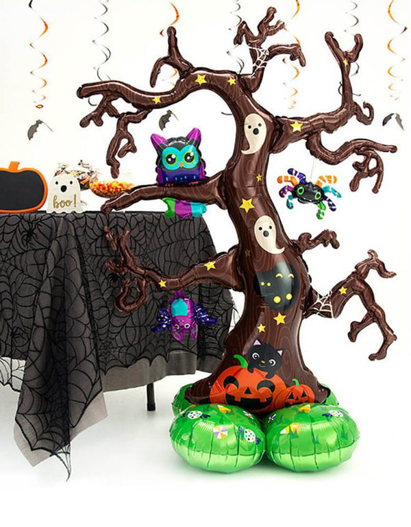 Anagram 62″ Creepy Tree Airloonz balloon Featuring owl, bat, spider and ghost, bat over a Creepy Tree, stands next to a halloween party table with black web table cover, candies, and pumpkin food jar. for a Halloween party, Haunted House Party.