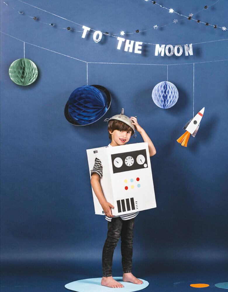 Kid wearing cardboard robot costume in front of To The Moon Garland