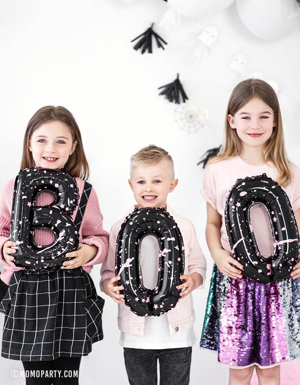 3 kids in a halloween party, each of them holding one letter of Party Deco - BOO Letter Foil Balloon Set.
