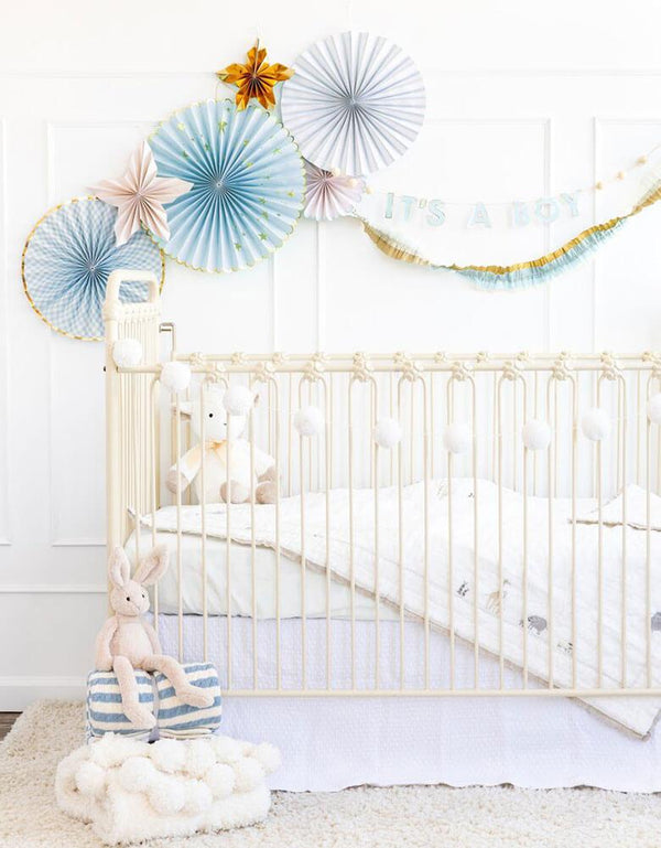 "Baby boy's nursery decoration ideas featuring my mind's eye baby blue paper fans and ""it's a boy"" banner on the wall"