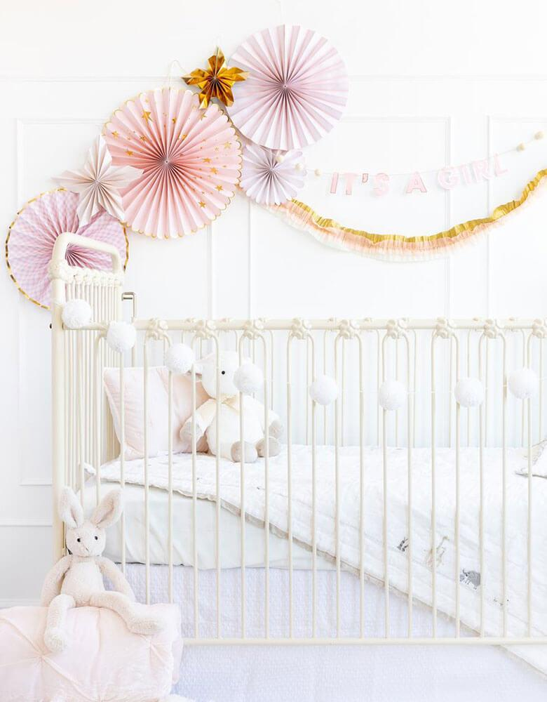 Baby girl's nursery decoration ideas featuring my mind's eye baby pink paper fans and it's a girl banner on the wall