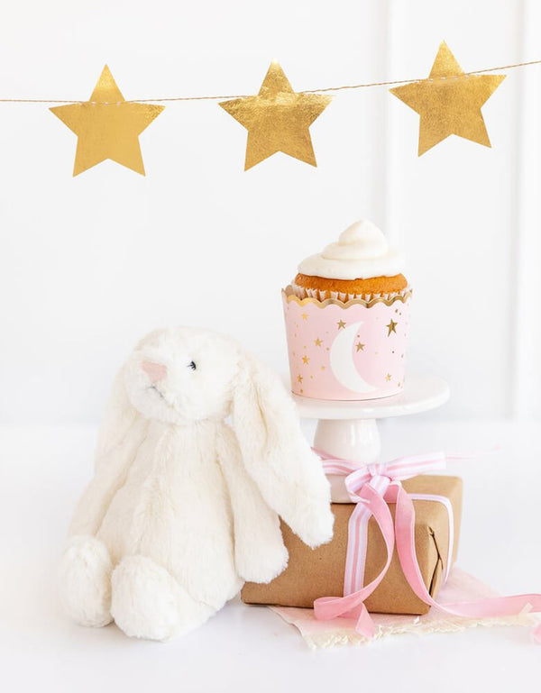 My Minds Eye Baby Pink 5 oz Food Cup with a cupcake next to a white stuffed bunny decoration with gold star party banner on the wall for a baby girl shower