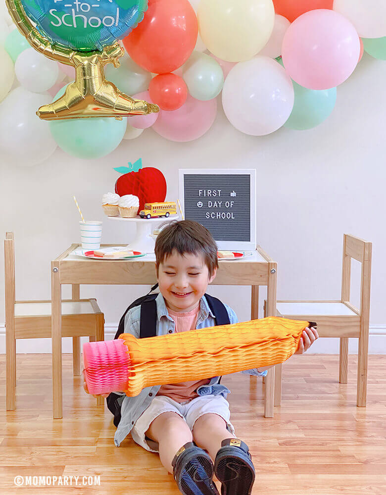 "Boy wearing back pack Boy at his 1st day of school celebrationplaying with a Devra Party 24"" Back To School Pencil Shaped Honeycomb Decoration"