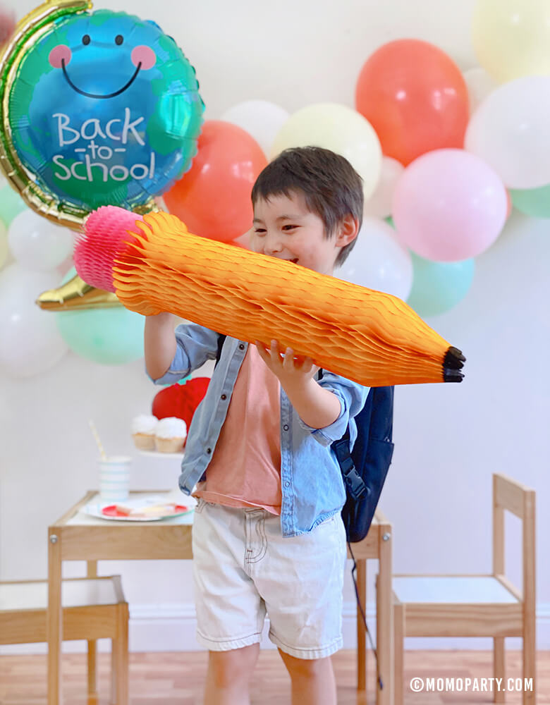 "Boy holding a Devra Party 24"" Back To School Pencil Shaped Honeycomb Decoration at his Back to School party, a 2020 Quarantine back to school home Party, modern Back to school party celebration."