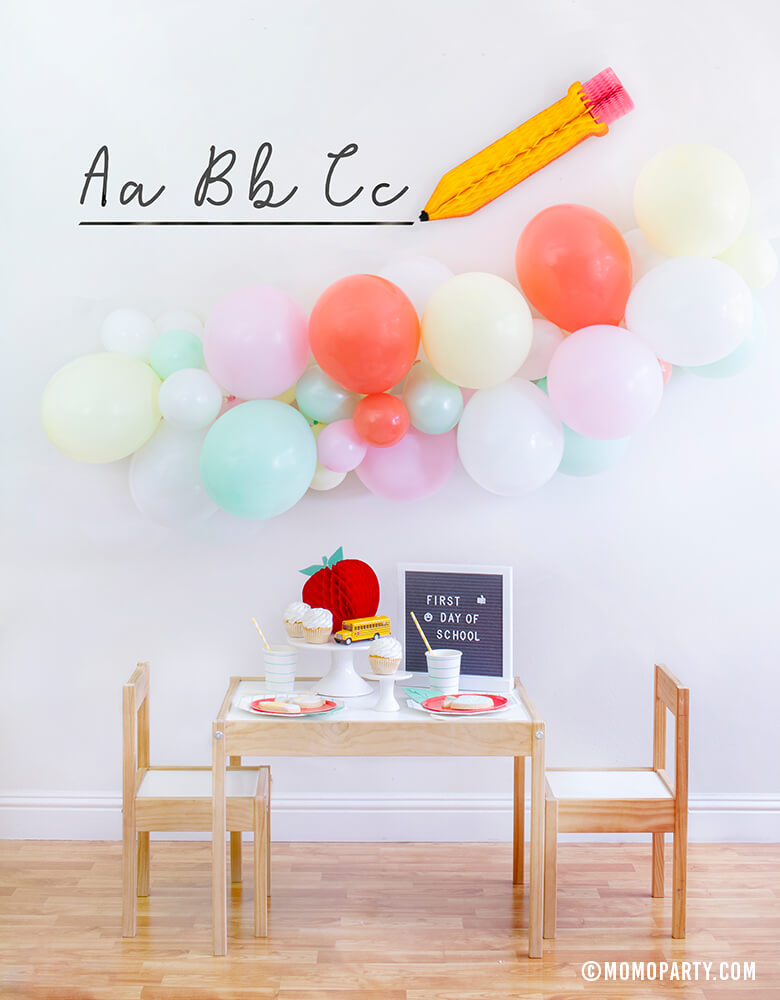 "Momo party Modern Back To School Party inspiration with a 6ft long Balloon Garland Assorted in Pastel Yellow, Pink, Mint, Carol, White Latex Balloon Pencil Honey Comb with ABC sticker as Backdrop decoration, Letter board with ""First Day of School"" sign, Oh happy day Cherry Red side plate, Aqua Striped Large Plates and cups, Leaf Napkins as tableware, Honeycomb Apple, cupcakes, and school bus toy on cake stand for a Modern Back to school Party Celebration"