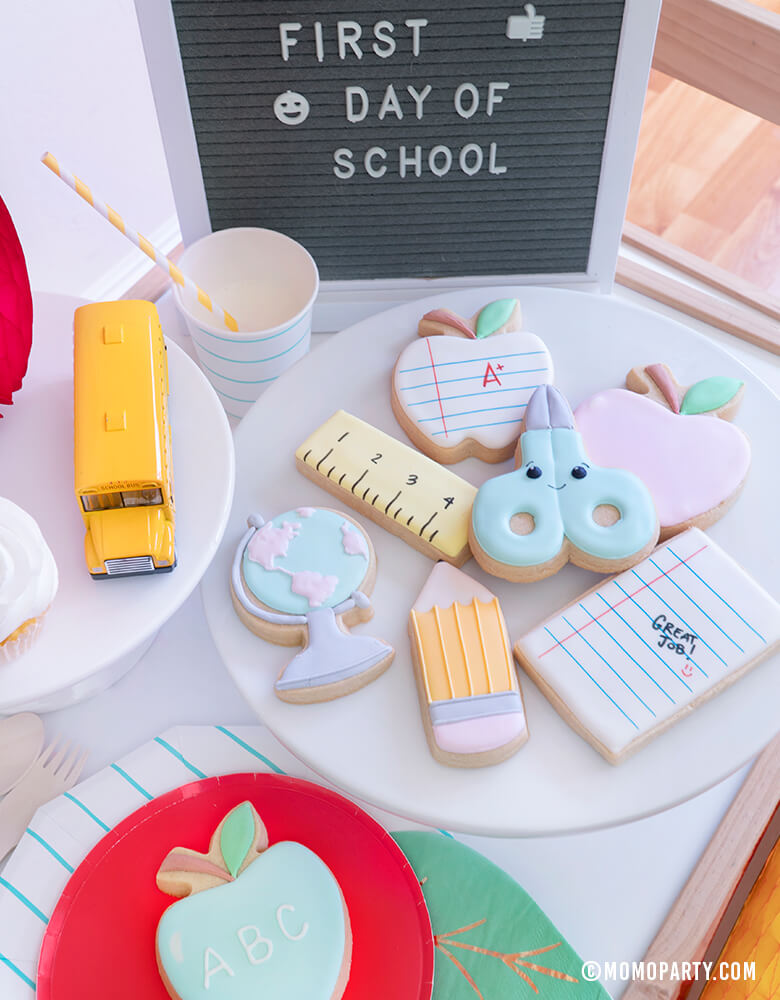 "Momo party - Morden Back To School Party Table Ideas with Back to school themed cookies, Oh happy day Cherry Red side plate, Aqua Striped Large Plates and cups, Leaf Napkins, Letter board with ""First Day of School"" sign, cupcakes, and school bus toy on cake stand as tableware"