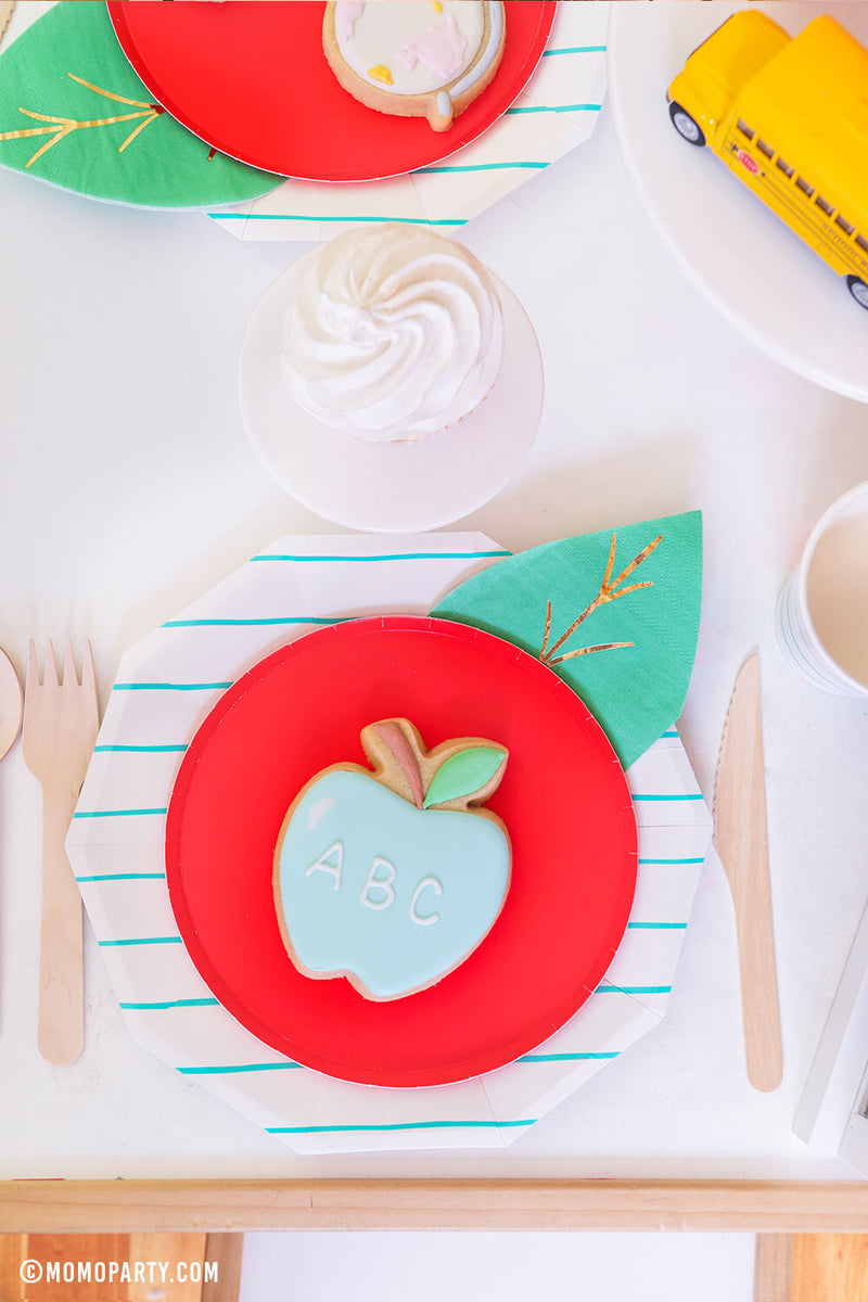 a Top view kid's table with a pastel ABC Apple cookie on top of Oh happy day Cherry Red side plate with Meri Meri Leaf napkin represent as Apple. Day Dream Society Aqua Striped Large Plates, wooden cutlery, cupcakes, school bus toys for a modern Back to school party celebration. 2020 Quarantine back to school home Party