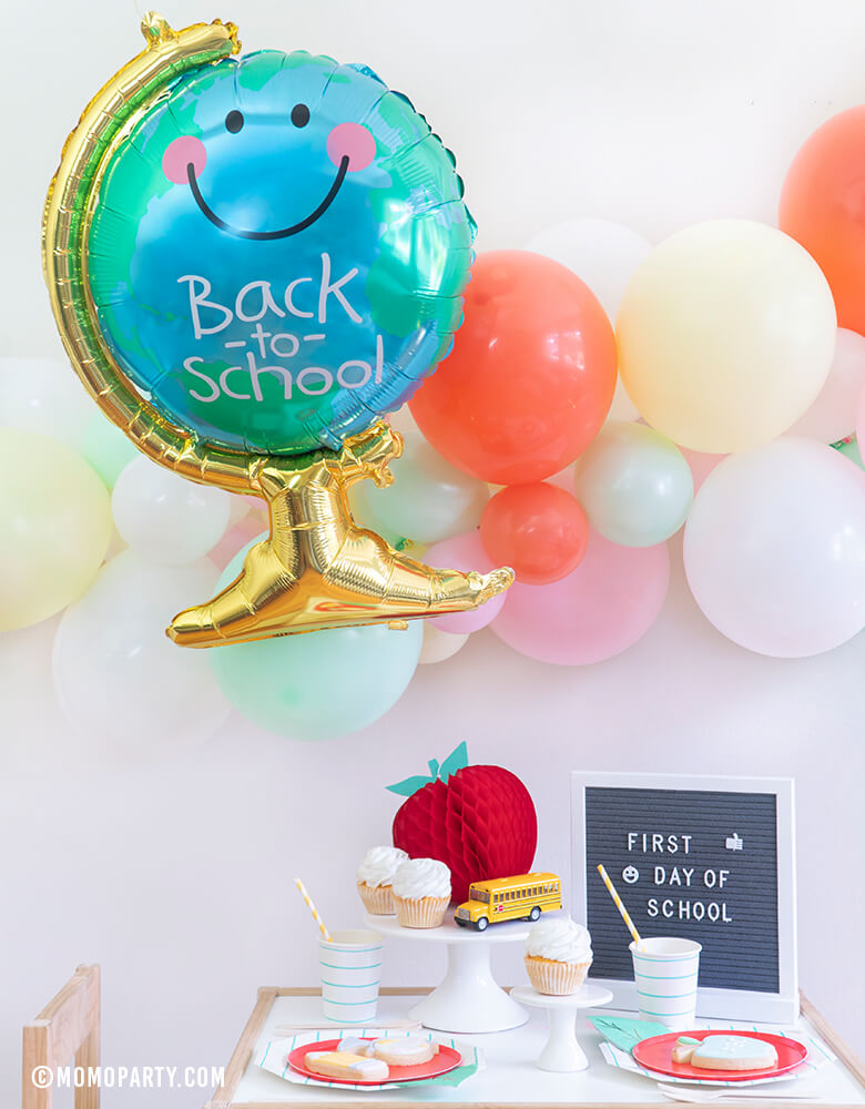 "Momo party - Morden Back To School Party inspiration with Anagram Back To School Globe Foil Mylar Balloon, 6ft long Balloon Garland Assorted in Pastel Yellow, Pink, Mint, Carol, White Latex Balloon for Backdrop decoration, Letter board with ""First Day of School"" sign, Oh happy day Cherry Red side plate, Aqua Striped Large Plates and cups, Leaf Napkins as tableware, Honeycomb Apple, cupcakes, and school bus toy on cake stand"