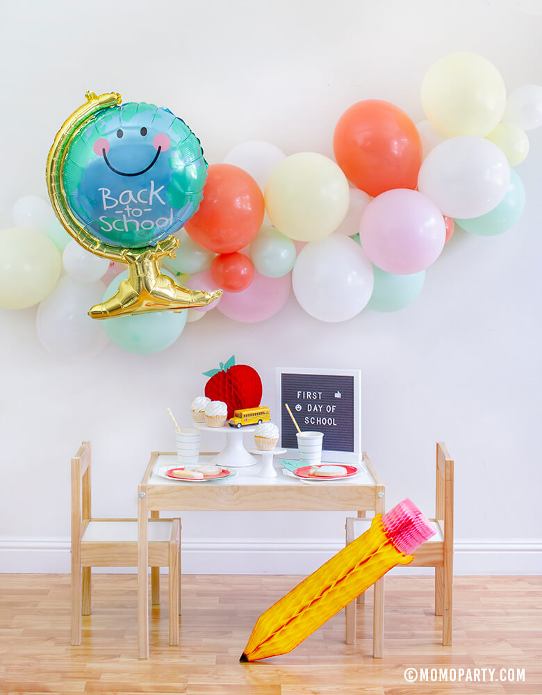 "Momo party Back To School  Party Box with Anagram Back To School Globe Foil Mylar Balloon, 6ft long Balloon Garland Assorted in Pastel Yellow, Pink, Mint, Carol, White Latex  Balloon for Backdrop decoration, Letter board with ""First Day of School"" sign, Oh happy day Cherry Red side plate, Aqua Striped Large Plates and cups, Leaf Napkins as tableware, Honeycomb Apple, cupcakes, and school bus toy on cake stand for a Modern Back to school Party Celebration"