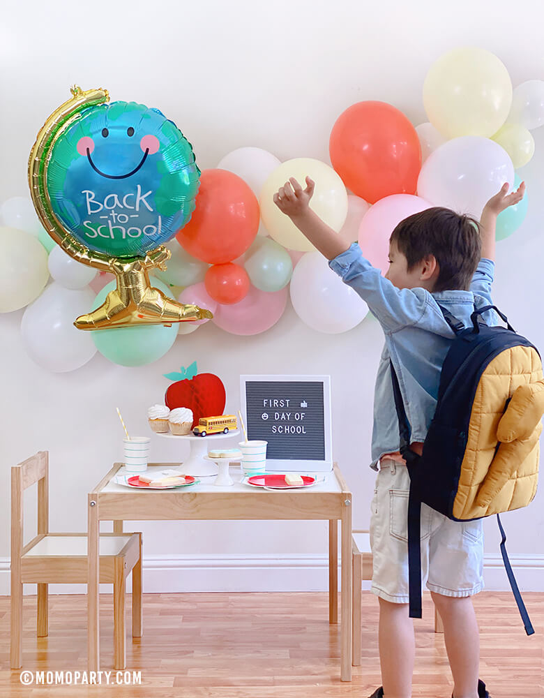 "A Happy Boy wearing a backpack celebrate  his Back to School party at home celebration with Anagram Back To School Globe Foil Mylar Balloon, pastel ballon garland, honeycomb apple, letter board with ""first day of school"", Mint stripe cups, plates..."