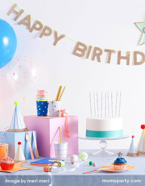 modern kid birthday party with Meri Meri Gold Happy Birthday Garland, a clean white and mint color cake with candle on the dessert table, with party hats , gifts, bright star color plates, jazz star napkins on the table