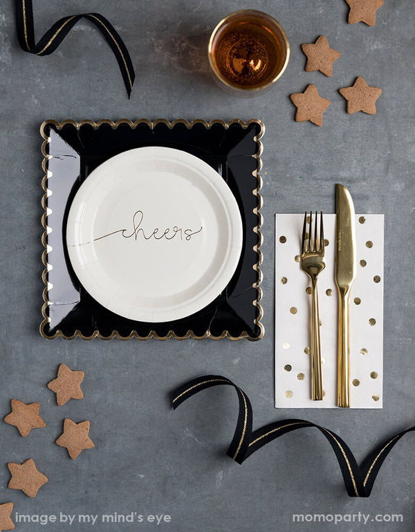 Elegant Graduation gatherings table top with my mind's eye Cheers small Plates paired with Black Scalloped Large Plates, gold polka dot napkins with golden cutlery on top, some star shaped cookies, a glasses of drink, black and gold ribbons around. Make your Celebration in style