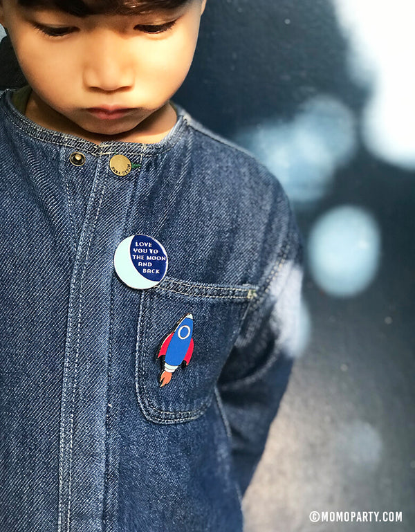 "Boy wearing  My Mind's Eye ""rocket-ship"", ""love you to the moon and back""  Space Blast Off Enamel Pin on his jumpsuit"