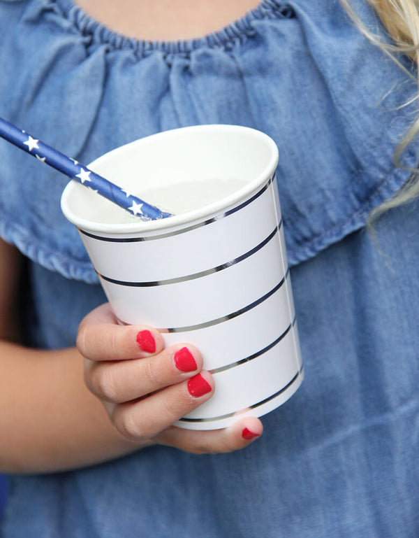 a Girl wearing a blue denim dress, and red nail polish, holding Day dream society Blue striped Party paper Cup with a blue stars paper straw in a 4th of july party celebration