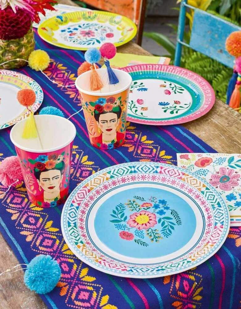 "A Boho Fiesta Themed Party Table featuring Talking Tables 9"" Boho Fiesta Floral Plates and Napkins with treats and pom pom food picks with a Mexican blanket beneath it"