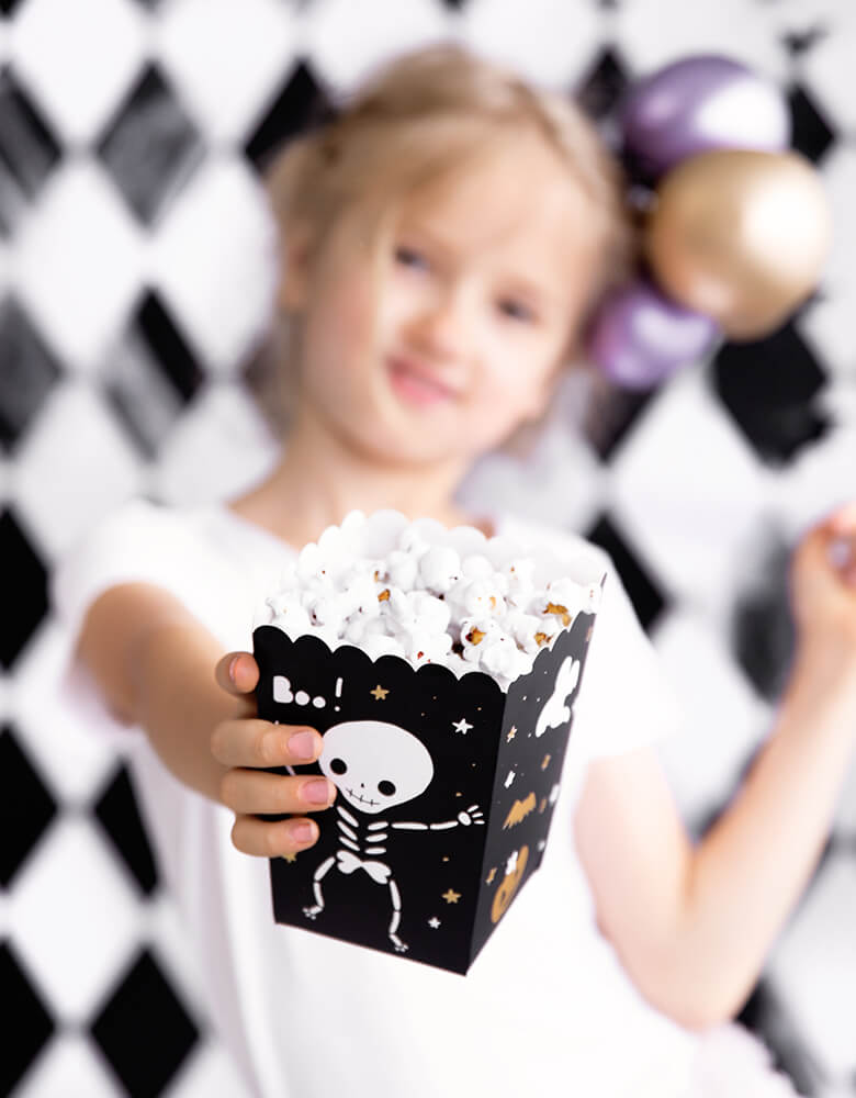 Little girl showing her Party Deco Boo Treat Favor Box filled with popcorns. This party treat box Feathering a cute black box with cute skeleton, Boo! ghost and gold pumpkin and bat design. These treat boxes are simply boo-riffic! Great for party treats like candies, popcorns and more. Or use them as favor boxes with goodies to send your little ghost home!