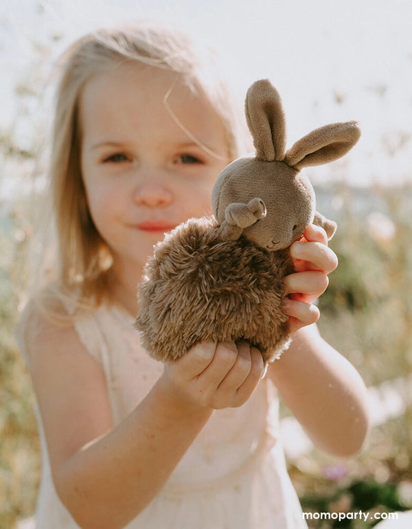 a little girl holding a cute Bunnies by the By - Roly Poly Brownie Plush. Soft round fur bodies with velour faces and dangly arms and legs. Embroidered faces and our signature blushed cheeks. This little bunny makes a perfect filler for your little one's Easter basket!