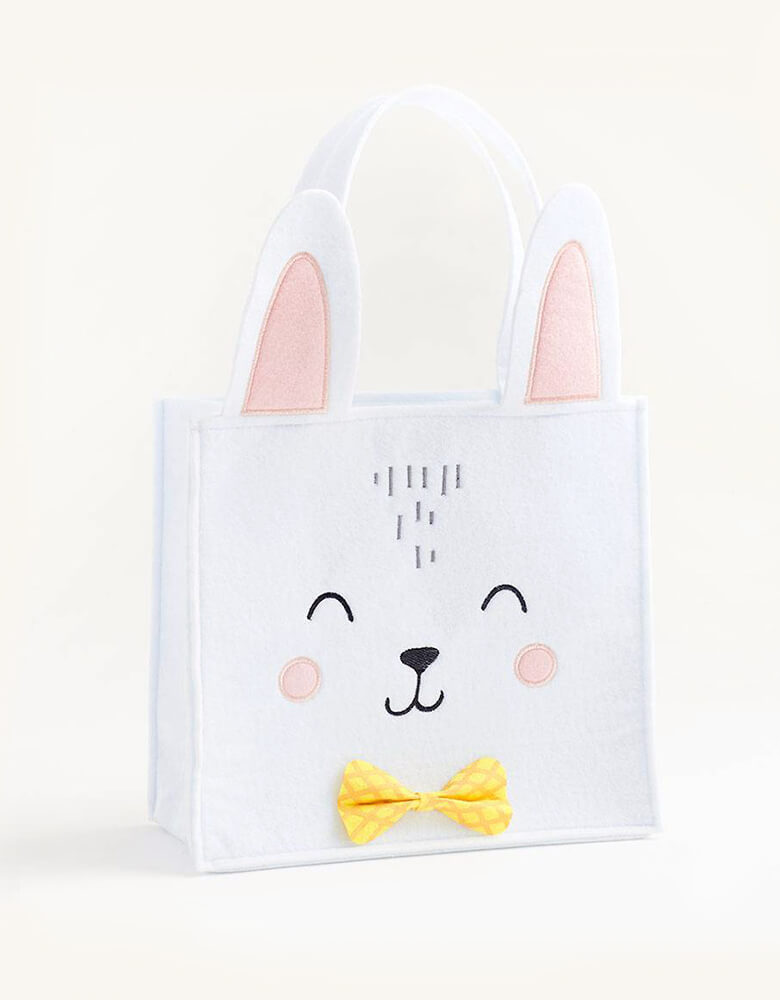 Paper Source - Bunny with Bowtie Basket. This sweet felt Paper Source designed Bunny Easter Basket features a smiling bunny with pink cheeks and ears, a yellow bowtie, and a cute white pom tail.