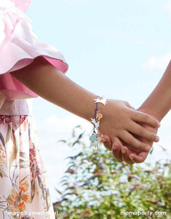 2 girls holding hands with wearing Meri Meri Bunny Enamel Bracelet with with adorable enamel bunnies and flowers and a bold blue cord and gold tone chain