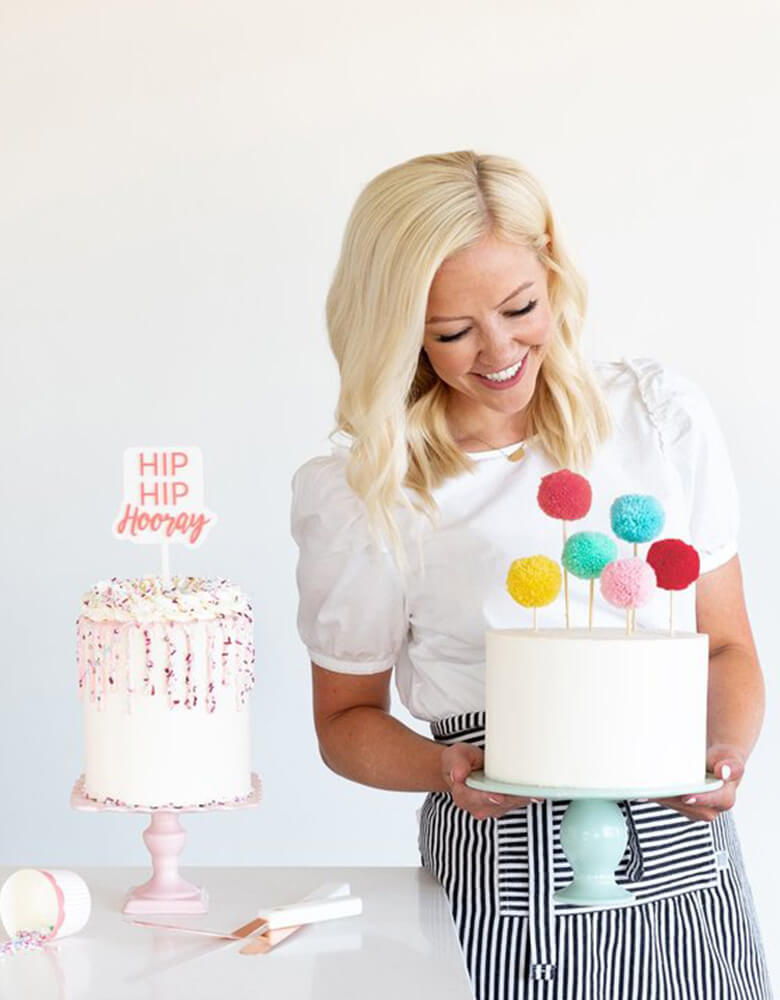 Courtney holding her cake dressed with the Pom Pom Cake Toppers by Mind Mind's Eye