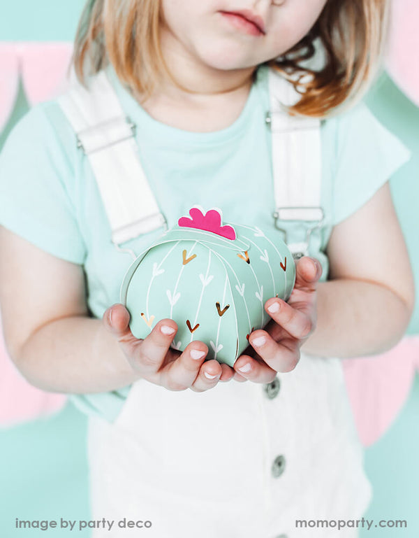 A girl holding a Party Deco Cactus Favor Boxes. This pastel mint Cactus-shaped party supplies are sure to spice up your fiesta party décor. and gift them to guests as they leave the fiesta.