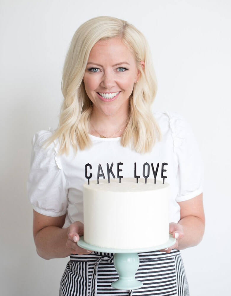 Courtney holding a cake with my mind's eye's black Letter-board Cake Toppers on it