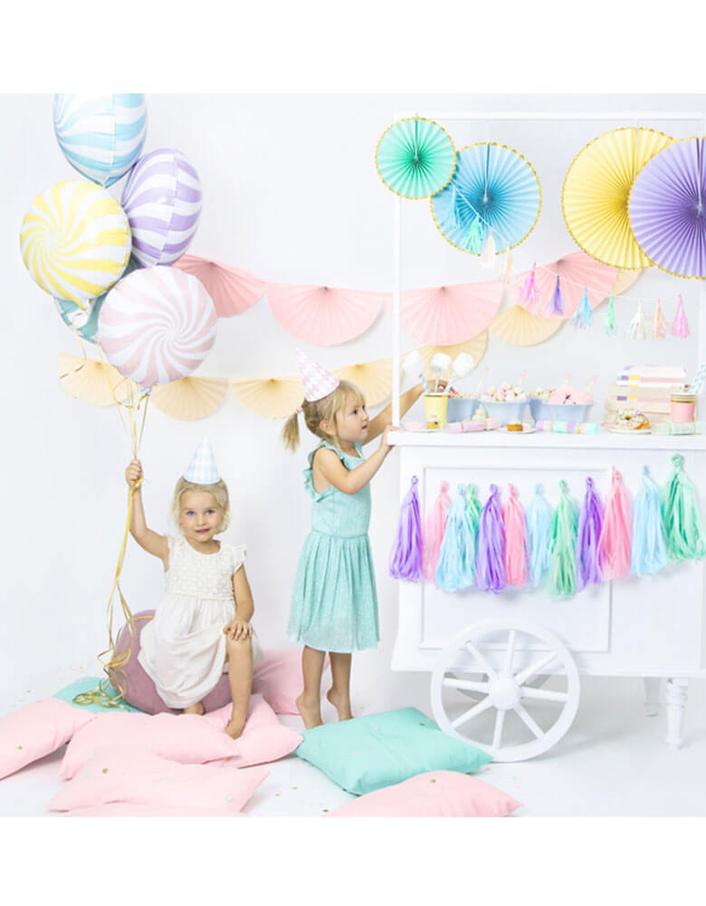 A sweets themed party with candy foil balloons and dessert cart filled with pastel decorations