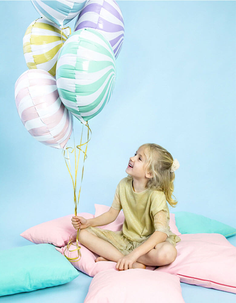 Girl holding assorted candy foil balloons by Party Deco