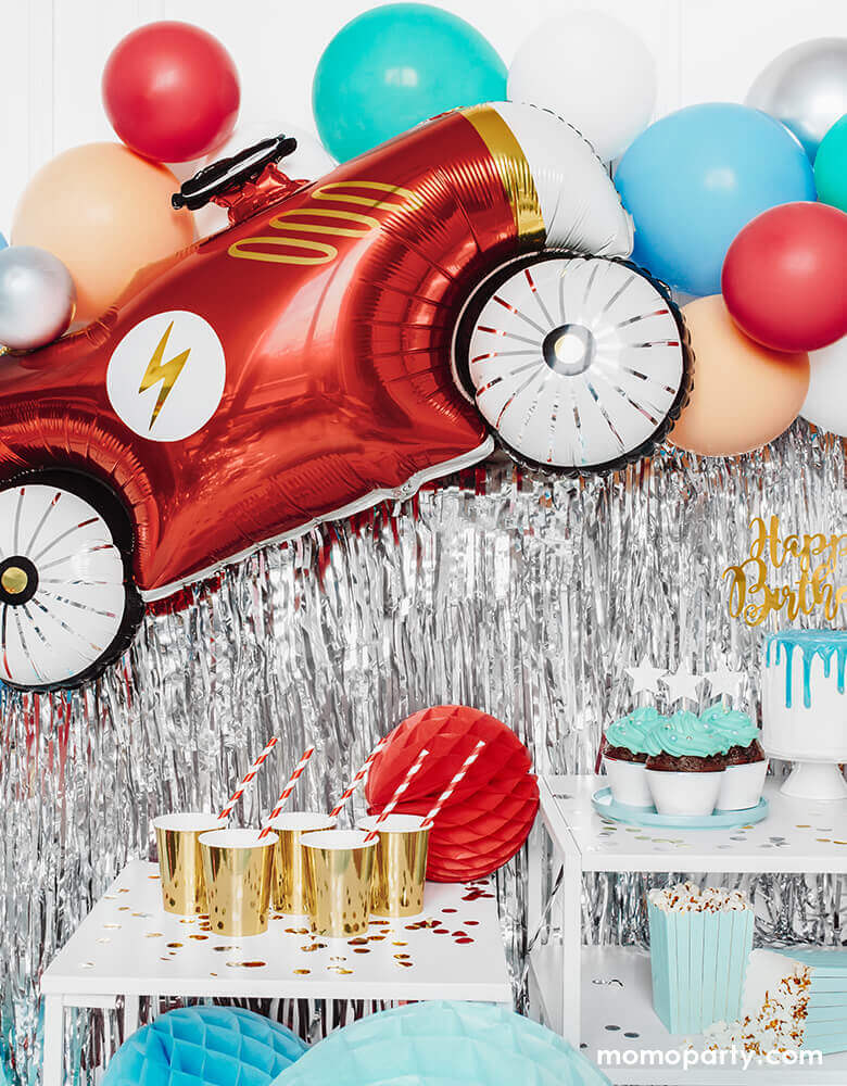 Car themed birthday party with Party Deco - 36inch Car Foil Mylar Balloon,  with a lighting icon on it's red car body with gold foil details. red, mint, blush and red balloon garland, silver curtain, red honeycomb, gold cups with red stripe party straws for a race car themed birthday party