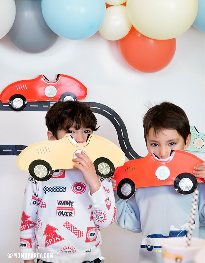 two boys boy play with MeriMeri Car Plates in front of Road tape decorated backdrop with matt blue, coral, matt yellow balloon garland, in a race car birthday party