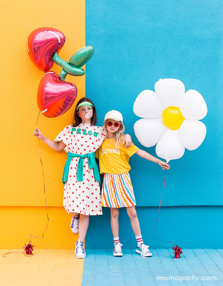 2 cool girls holding Cherry Foil Balloon and Daisy Foil Mylar Balloon by Party Deco, in front of colorful painted wall.  These adorable Daisy petal shapes and cheery shaped foil mylar balloons bright your summer celebration