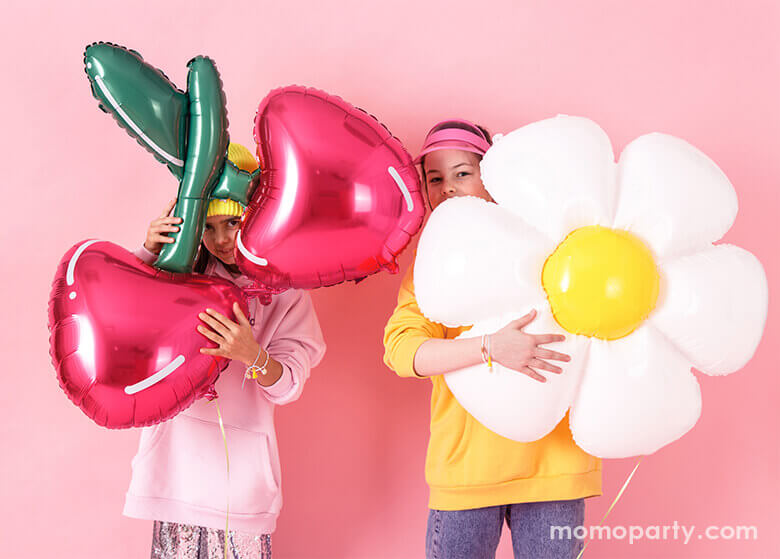 Two girls hugging Cherry Foil Balloon and Daisy Foil Mylar Balloon by Party Deco, in front of pink wall. these fun shaped balloons so bright the summer celebrations
