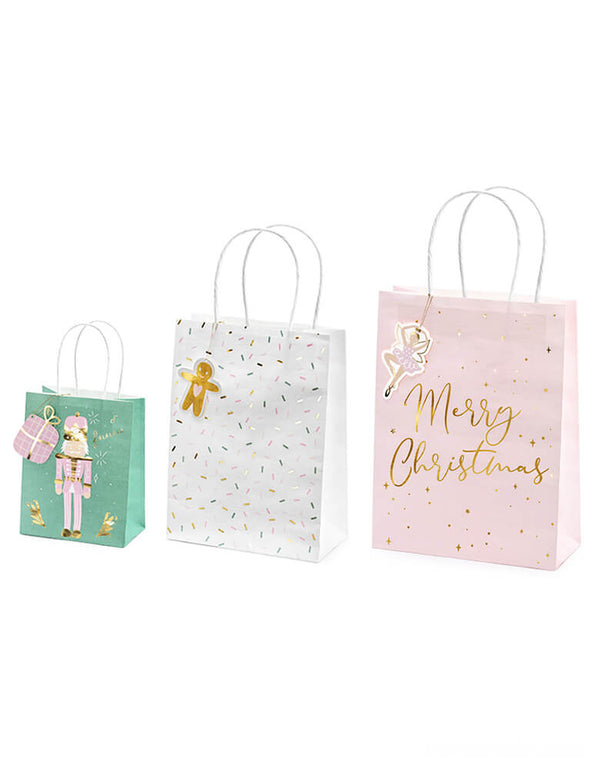Party Deco Christmas Gift Bags, Set of 3, contains 3 designs including pink nutcracker over green bag, gingerbread man on the sprinkles white bag, and pink ballerina on the Pink bag with gold foil Merry Christmas sign. Each bag comes with a gift tag to write on it!
