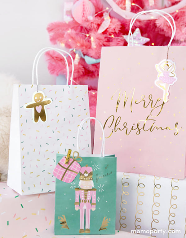 Closet up details of Party Deco Christmas Gift Bags and gift boxes under the Pink Christmas tree. These 3 designs party bags with gift bag shaped gift tag on the pink nutcracker illustrated green bag, gingerbread man gift tag on the sprinkles white bag, and pink ballerina gift tag  on the Pink bag with gold foil Merry Christmas sign.