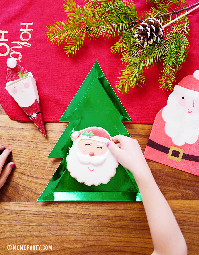 gril's hand putting Santa cookie on top of  Christmas Tree Paper Plates