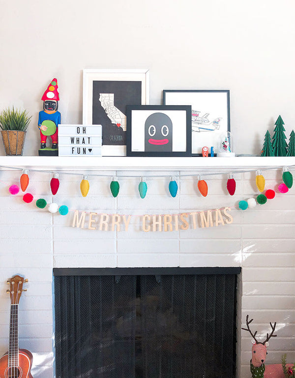 Christmas decoration with Festive Pompom Garland over the fireplace