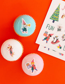 blue, Pink and white cupcakes decorated with Make Bake shop Christmas Is Awesome! Edible Decorating Stickers, include edible stickers with many cute christmas design like a christmas dancing dog, penguin, koala with christmas sweaters,  christmas trees, gifts, candy cane, designed by Hello!Lucky for Make Bake. . Simply peel it and apply to iced cakes, cupcakes, cookies, These easy baking hacks will be These editable stickers make decorating baked goods so much easier this Holiday season