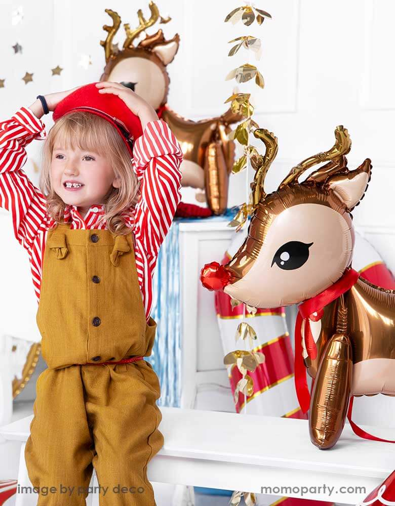 "A girl in candy cane red striped shirt sitting next to party deco's 24"" reindeer foil balloon in a Christmas party"