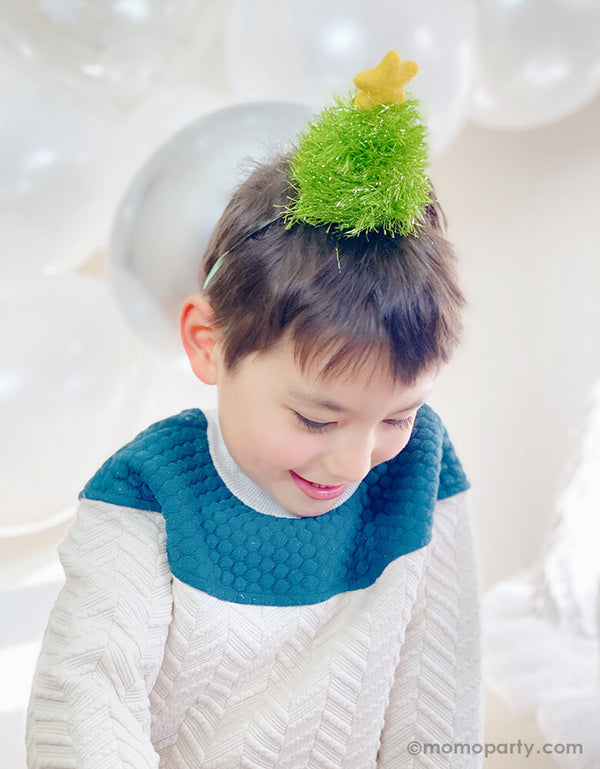 boy wearing a Christmas-Tree-Glitter-Hat with silver white balloons for a white christmas party celebration