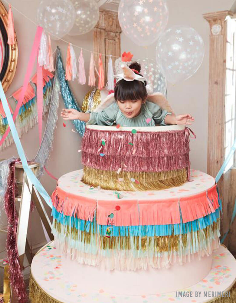 Kids Birthday party with a birthday cake decorated with Meri Meri's Colorful Fringe Large Garland