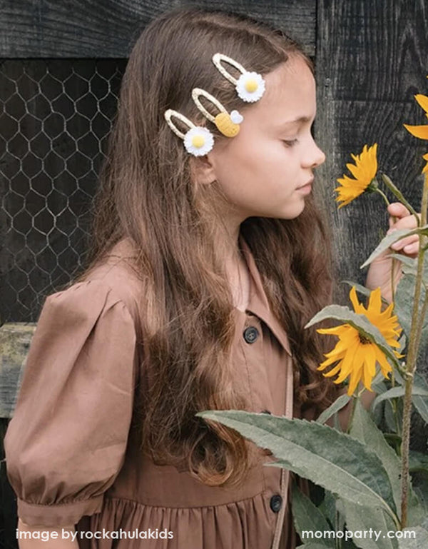 Girl wearing a Rockahula Kids Daisy Pom Pom Hair Clips and Bertie Bee Hair Clip, in the garden smelling sunflowers